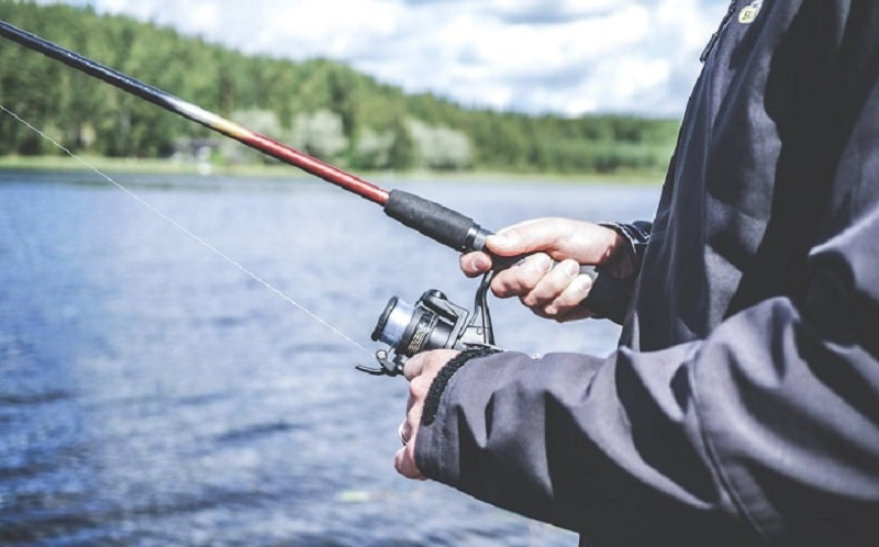 Man Holding Fishing Rod with Micro Spinnign Reel